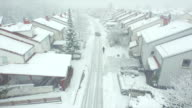 AERIAL: Lonely person walking through suburban town in snowstorm video