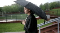 Lonely sad woman standing on the street under heavy rain. video