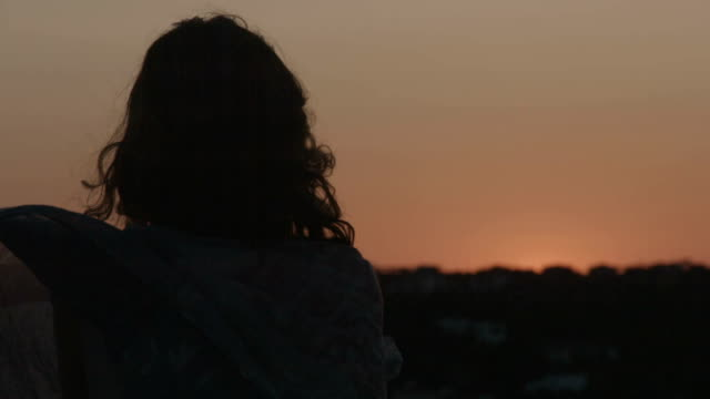 Lonely woman looking at burning sky at sunrise, sunset. Hair video
