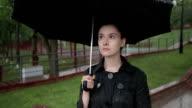Lonely woman standing on street in heavy rain. Slow motion video