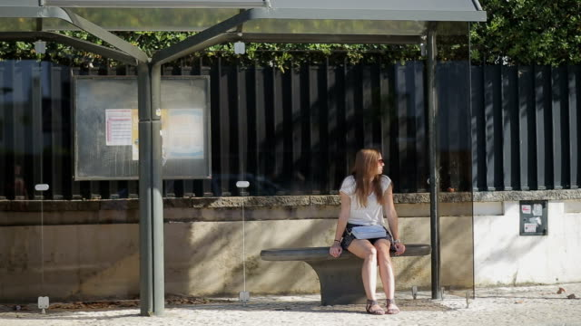 Lonely young girl waiting at bus stop in skirt, summertime video