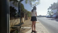 Lonely young girl waiting staying at bus stop with smart phone in blue skirt and sunglasses, summertime, traffic video
