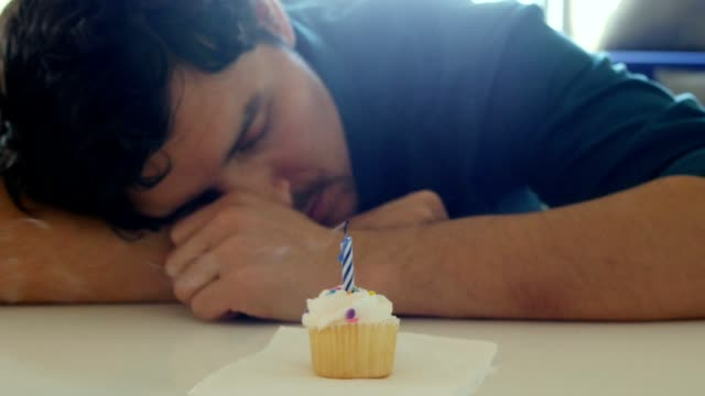 Lonely young man blowing out birthday candle on cupcake and making a sad face video