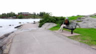 Lonely young woman sit on bench at stony shore, fresh breezy place video