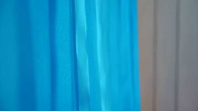 Long bright blue ribbons hanging on wall background for party video