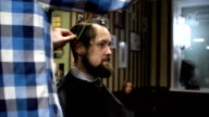 Long hair Barber cuts the hair of the client with scissors and comb in his barbershop video