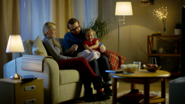 Long Shot of a Father, Mother and Little Girl Watching TV. Father Explains Something to His Little Girl. They Sit on a Sofa in Their Cozy Living Room. It's Evening. video