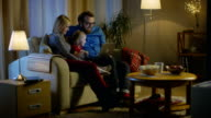 Long Shot of a Father, Mother and Little Girl Watching TV. They Sit on a Sofa in Their Cozy Living Room, Father Holds Laptop on His Knees. It's Evening. video