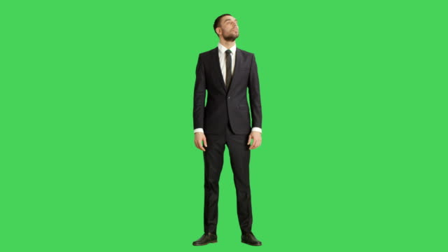 Long Shot of a Handsome Smiling Businessman Amusingly Looking Around. Shot on a Green Screen Background. video