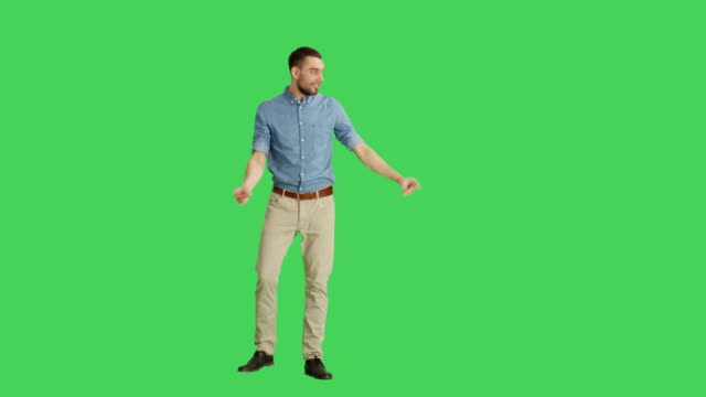 Long Shot of a Handsome Smiling Handsome Man Making Finger Guns/ Presenting Gesture. Background is Green Screen. video