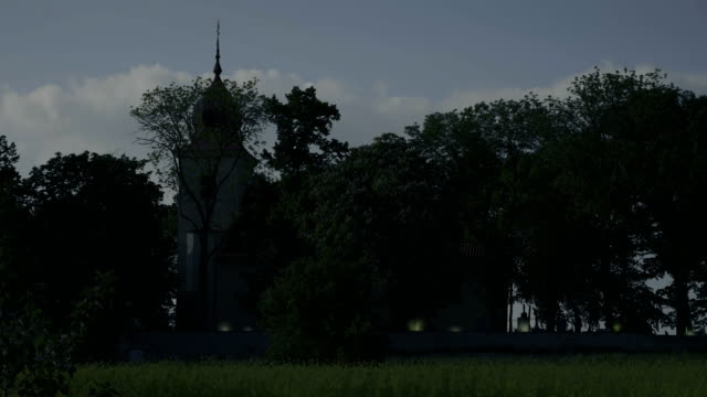 Long shot to small church with bell tower and cemetery, raging candles on graves. video