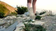 Long Slim Beautiful Female Legs In Sneakers Walking On The Rocky Road And Stops At The Top of The Mountain video