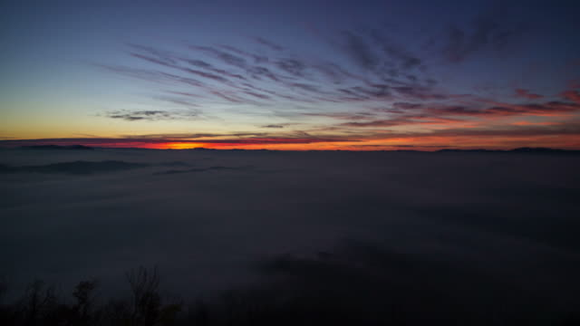 Long sunrise over foggy valley time lapse video