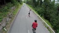 AERIAL: Longboard skaters driving down the road in slow motion video