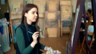 Long-haired girl paints with oil colors on easel in workshop interior video
