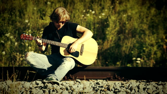 Long-haired teenage guitarist strums an acoustic guitar sitting on the railway video