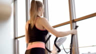 Look of the girl working out with the simulator in the modern gym FullHD video