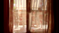 Looking out through open glass door with waving curtain at man drinking coffee video