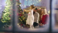 Looking Through Snowy Window. Happy Family: Father, Mother and Their Little Daughter are Decorating Christmas Tree. video