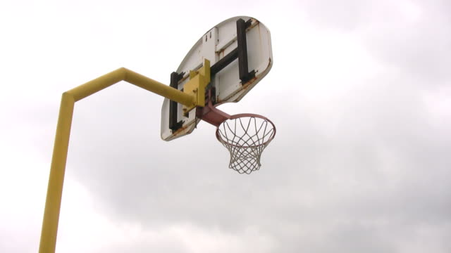 Looking up at outdoor basketball net and panning video