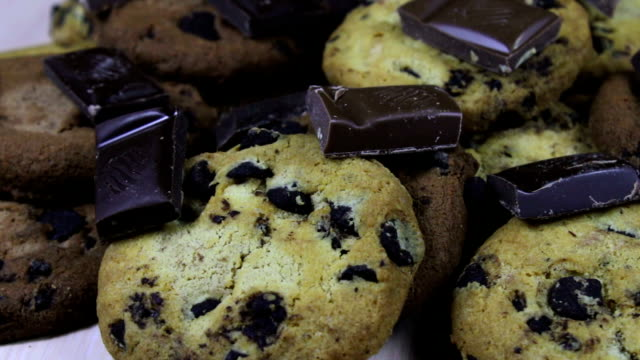 Lot of chip cake cookies with chocolate close-up tilting and Pieces of milk and dark chocolate video