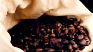lot of coffee beans falling down in a canvas sack video