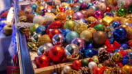 A lot of colorful Christmas tree decorations being sold on a Christmas market video