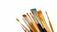 Lot of different paints and brushes on white background, slow motion video