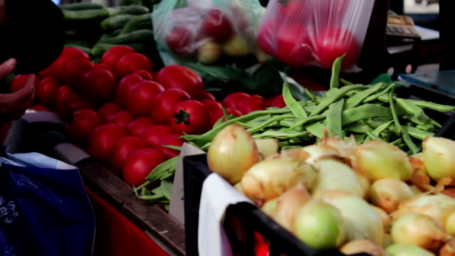 Lot of fresh vegetables on the market counter. Buyers look at the choice of fresh tomatoes, potatoes, peppers, beans, cherries, bananas. Buyer and seller in the market. People choose food products video
