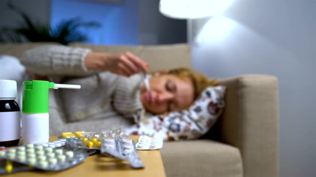 A Lot Of Pills And Medicines On A Table In Front Of A Sick Young Woman On Couch video