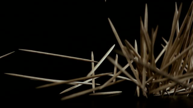 A lot of toothpicks fall down on a black background. Slow motion video