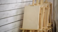 Lots of wooden easels stand in corner of workshop video