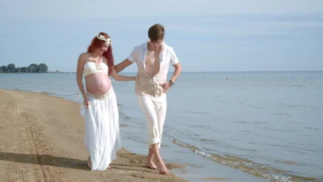 Love couple drawing on beach. Romantic couple having fun on sea beach video