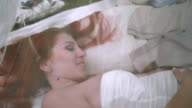 Love couple relax behind white transparent fabric in park. Love couple relaxing video