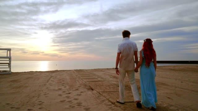 Love couple walking on sea beach at sunrise. Couple beach video