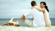 Lovely couple hugging and talking on the beach by fire video