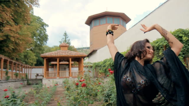 Lovely girl dressed in costume for oriental dance with a black veil on her shoulders womanly moves in the garden with red roses in slow motion video