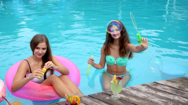 Lovely girls sitting at Inflatable ring in pool and do bubbles, Summer party, Friends In bathing suit resting video