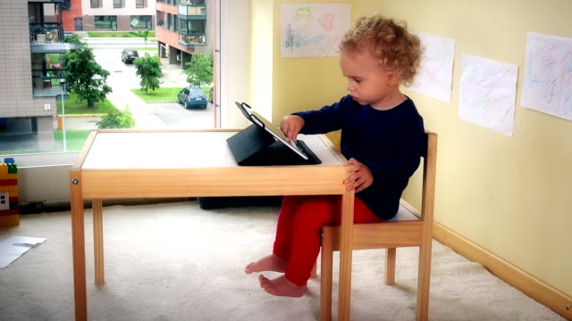 Lovely kid playing with tablet pc sitting on small chair near table. video