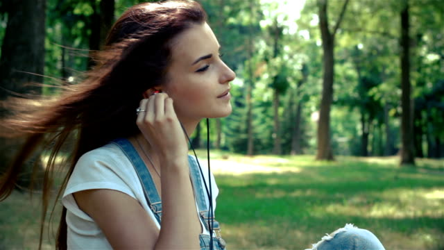 lovely young brunette inserts earphones in her ears and listens to music video