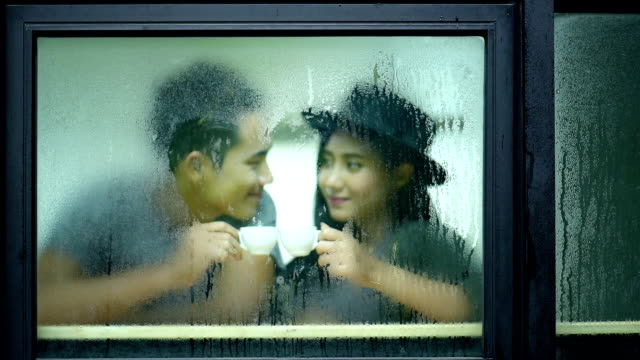 Lover writing heart on raindrop window video