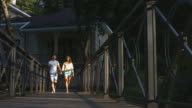Lovers guy and girl walking on a bridge in the park. video