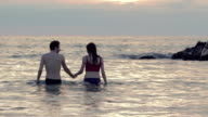 lovers walking into the sea at sunset holding hands and kissing each other video