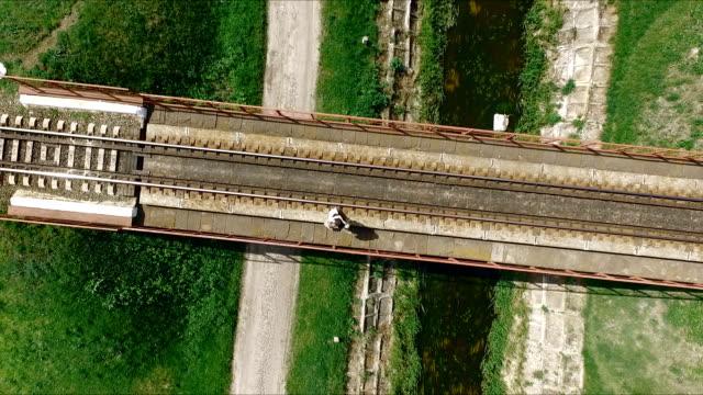 lovers walking on a railway bridge - aero video