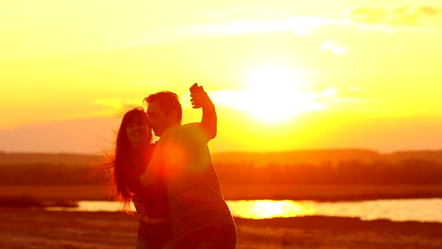 Lovers whirl at sunset and make selfie video