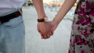 Loving couple are holding hands. Slow motion video