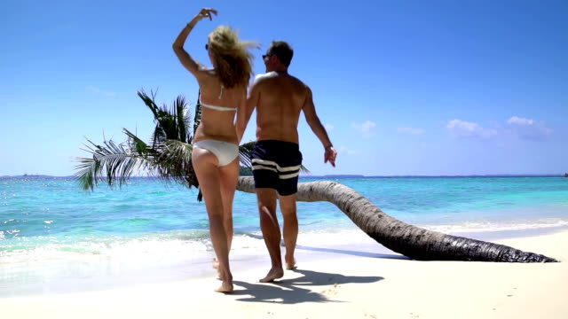 A loving couple enjoying vacation on a tropical beach. Slow motion. video