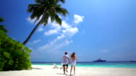 A loving couple enjoying vacation on a tropical beach. Slow motion video