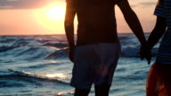 Loving couple holding hands by rough wavy sea at sunset video