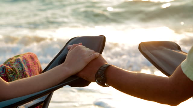 Loving Couple Holding Hands While Sitting On Outdoor Chairs At Seashore video